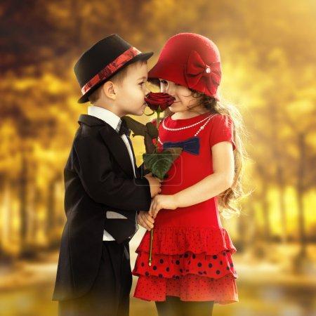 Photo pour Charmant petit garçon donnant une rose à la fille à la mode et son excité. Concept d'amour - image libre de droit