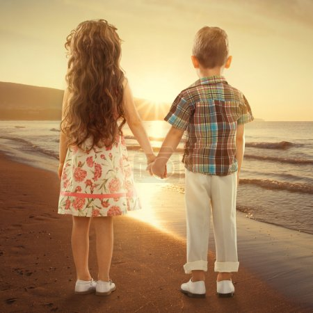Photo for Back view of little girl and boy holding hands at sunset. Love, friendship concept - Royalty Free Image