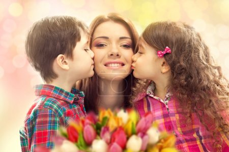 Photo for Portrait of children kissing her mother with flowers. Mothers day concept. Family holiday - Royalty Free Image