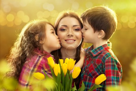 Photo for Portrait of children kissing her mother with flowers. Spring, March 8, International Womens, Mothers day, family holiday - Royalty Free Image