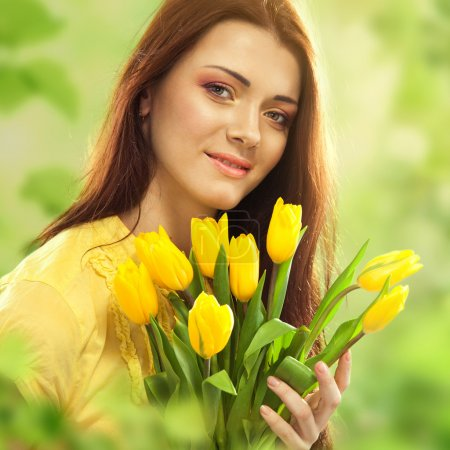 Beautiful woman with tulips bouquet of flowers