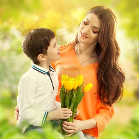 Son hugging his mother and gives her flowers