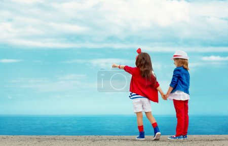 Fashion kids points to the sea