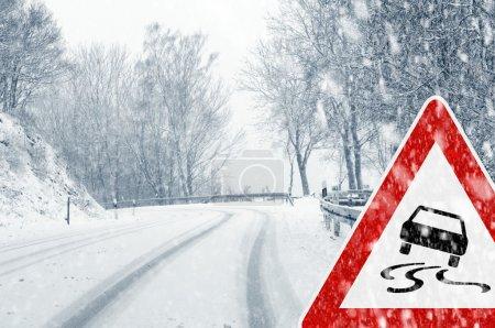 Photo pour Conduite en hiver - chutes de neige sur une route de campagne avec le panneau d'avertissement - image libre de droit