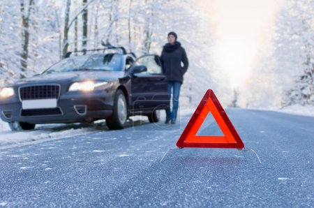 Photo for Car breakdown on a country road in winter. Woman standing beside her car and waiting for help. - Royalty Free Image