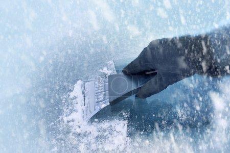 Photo pour Conduite hivernale - femme gratte la glace d'un pare-brise - image libre de droit