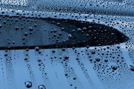 Gotas de agua en la pintura pulida del coche