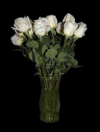 Photo pour Plusieurs belles roses blanches à longues tiges dans un vase en verre clair isolé sur un fond noir. Excellente image à utiliser pour la Saint-Valentin, anniversaires, cartes de voeux et plus . - image libre de droit