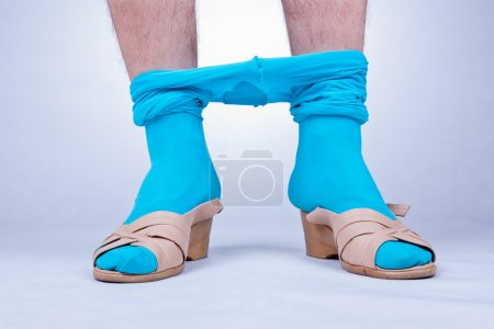 Photo for Front view of man's legs standing in female shoes and tights. - Royalty Free Image