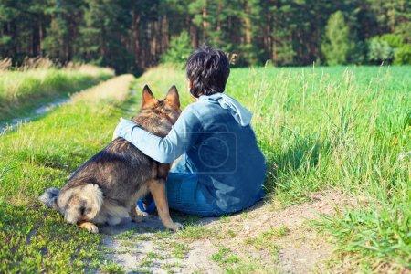 Photo pour Petit garçon assis avec son chien sur le pré sur appareil photo - image libre de droit
