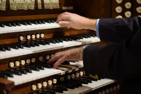 Photo pour Bouchent la vue d'un organiste jouant d'un orgue à tuyaux avec le flou de mouvement. - image libre de droit