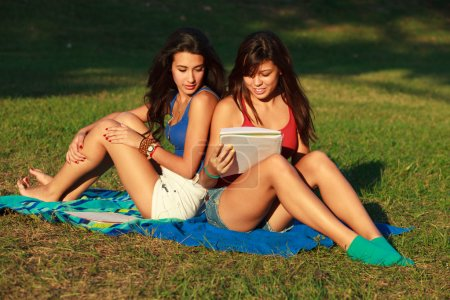 Photo for Beautiful multicultural young college women studying outdoors on campus. - Royalty Free Image