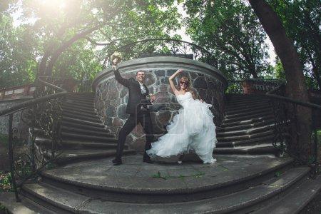 Photo pour Drôle de couple de mariage dansant sur un escalier . - image libre de droit