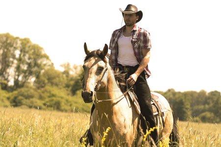 Photo pour Ridig homme jeune cowboy avec cheval - image libre de droit