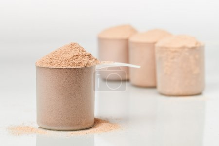 Scoop of chocolate whey isolate protein in front of three scoops of protein blurred in the background