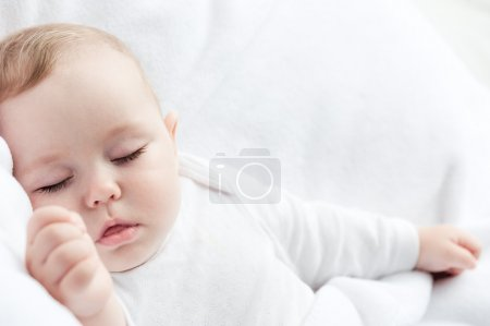 Photo for Carefree sleeping little baby on a bed - Royalty Free Image
