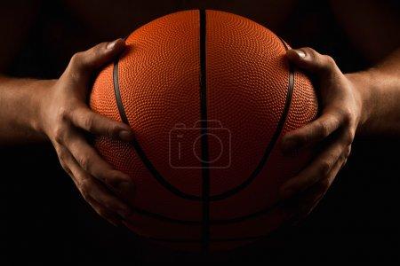 Photo pour Basket dans les mains de l'homme gros plan sur un fond noir - image libre de droit
