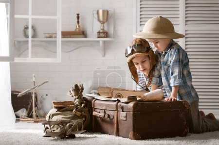 Boys travelers studying maps and  books