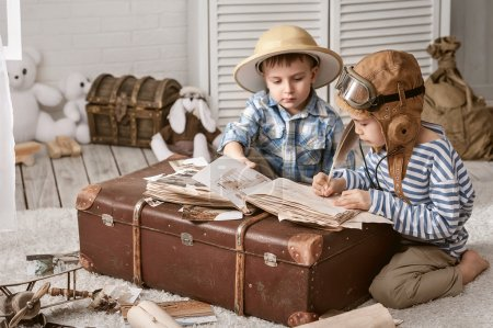 Photo for Two boys in the images of the pilot and the traveler fill their travel book - Royalty Free Image