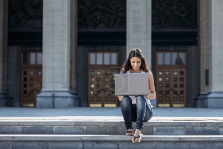 A young woman with a laptop sitting on the stairs, near the univ