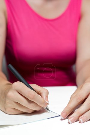 Photo for Woman's Hands With French Manicure Holding A Pen Writing A Text - Royalty Free Image