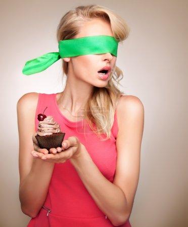 Blonde woman with cupcake posing.