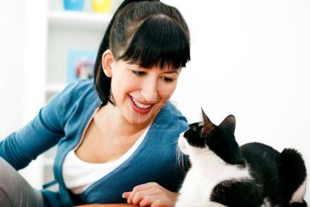 Photo pour Jeune femme profite du salon avec chat . - image libre de droit