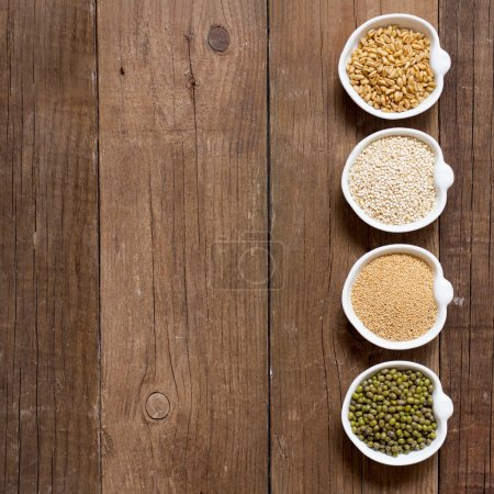 Photo for Raw Organic Amaranth and quinoa grains, wheat and mung beans in small bowls - Royalty Free Image