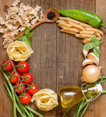 Nudeln, Gemüse und Kräuter auf Holz
