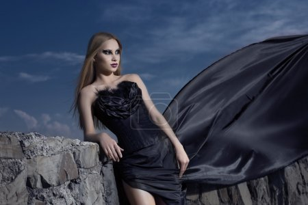 girl in a corset with a long train at the wall.