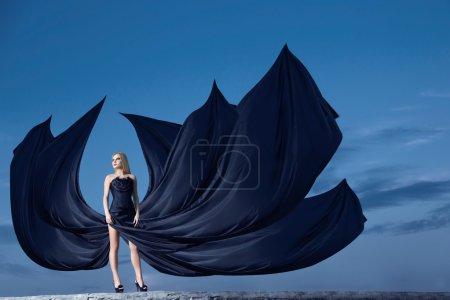 Photo pour Belle jeune fille dans un corset et robe avec une longue traine sur le mur de Pierre. fond de ciel de nuit. - image libre de droit
