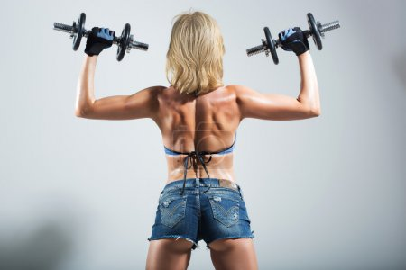 back of a muscular woman  with two dumbbells