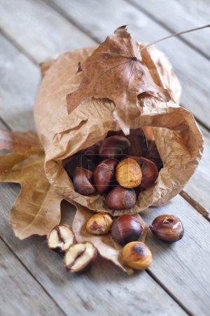 Photo pour Châtaignier rôti dans un sac papper sur une vieille table en bois . - image libre de droit