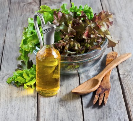 Photo for Green salad lettuce with olive oil on old wooden table. Selective focus. - Royalty Free Image