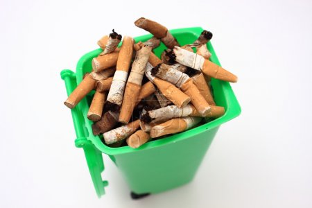 Used cigarette butts in green waste bin on white background