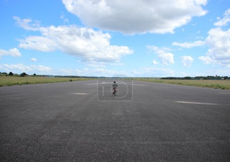 Photo for Biking child with helmet on airplane runway - Royalty Free Image