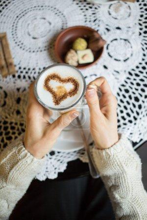 Frau mit heißer Tasse Kaffee in Herzform