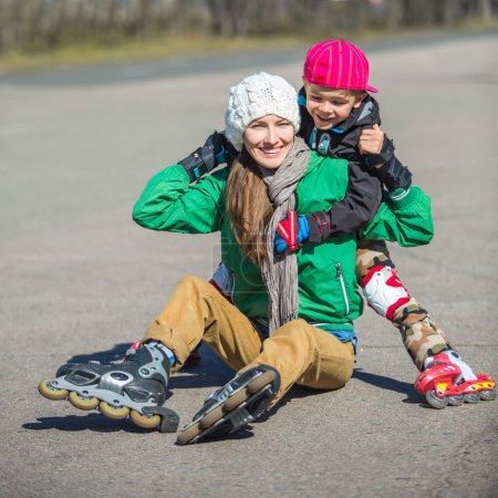 Photo for Active family - mother and kid having fun, rollerblading outdoor on a sunny spring day - Royalty Free Image
