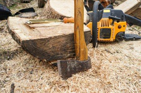 Photo pour Outils en bois - hache, lime à tronçonneuse et tronçonneuse en arrière-plan à l'extérieur. focus sur hache et bûche bois - image libre de droit