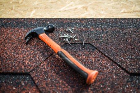 Photo pour Bardeaux d'asphalte sur une toiture de bois avec marteau et des clous - image libre de droit
