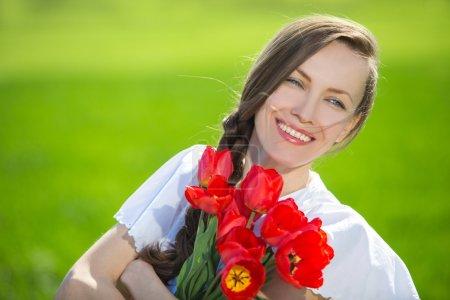 Photo pour Portrait de jeune femme belle avec fleurs heureux souriant, profiter de la nature sur la nature de fond vert été - image libre de droit