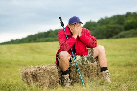 Traveler trekker enjoying a valley view while sitt...