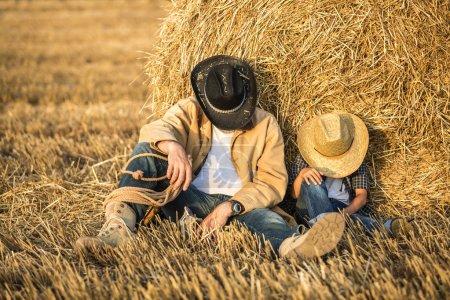 Photo pour Heureux père joyeux avec un fils mignon en chapeaux de cowboy, famille, voyage, vacances, fête des pères - concept. mettre l'accent sur le père - image libre de droit