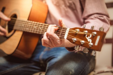 Portrait of man playing on acoustic guitar on sunny day