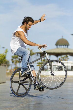 Photo for Young adult doing a trick on his fixie bicycle in a park of the city - Royalty Free Image
