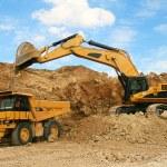 Backhoe loader loading dumper truck mining...