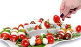 Ruční namáčení špíz cherry rajčaty a mozzarellou vin