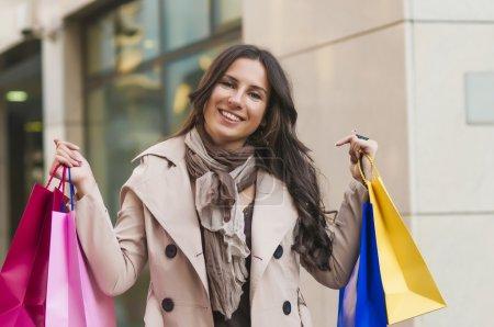 Photo pour Belle femme avec ses sacs à provisions devant un centre commercial - image libre de droit