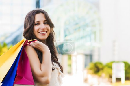 Photo for Beautiful woman with her shopping bags in front of a shopping centre - Royalty Free Image