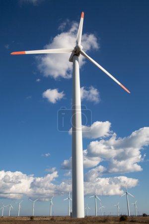 Wind turbine farm over the blue clouded sky